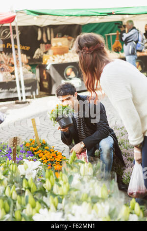 Woman looking at male friend smelling potted plant in market - Stock Photo