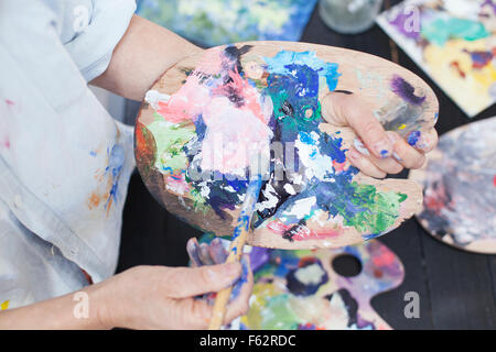 Cropped image of senior woman using palette and paintbrush - Stock Photo