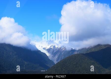 Beautifl Franz Josef Glacier on a sunny day with low lying fluffy white clouds - Stock Photo