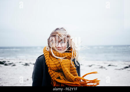 Portrait of young woman with tousled hair at beach - Stock Photo