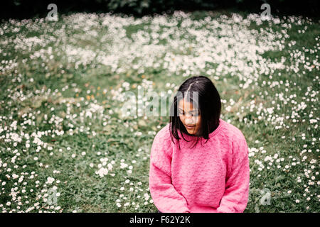 Happy young woman sitting on field in park - Stock Photo