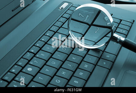 Magnifying glass on laptop computer. Toned in blue - Stock Photo
