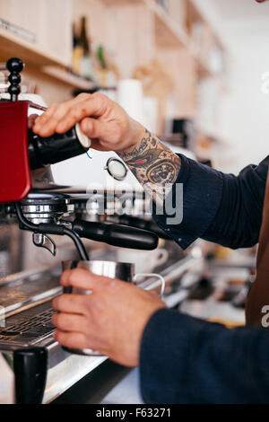 Cropped image of barista using coffee maker at cafeteria - Stock Photo