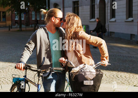 Young couple rubbing noses while holding bicycles on street - Stock Photo