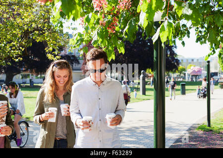 Couple holding disposable cups while walking on street at park - Stock Photo