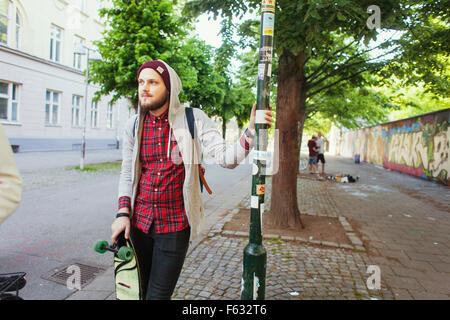 Thoughtful man with skateboard standing on sidewalk - Stock Photo
