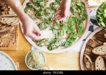 Cropped hands preparing open faced sandwiches at table - Stock Photo