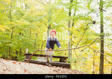 Happy girl carrying tree in forest - Stock Photo