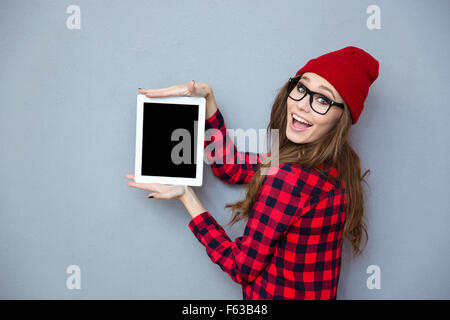 Portrait of a happy hipster woman showing blank tablet computer screen on gray background - Stock Photo