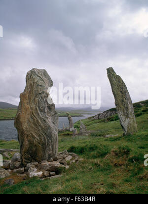 Looking WSW at four of five standing stones arranged in a semicircle on artificial terrace overlooking West Loch - Stock Photo