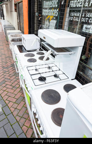 Second hand cookers, old white goods and other used domestic appliances for sale outside a shop on a UK town centre - Stock Photo