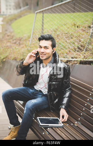 Young handsome indian contemporary businessman seated on a bench in a park using tablet talking smartphone with - Stock Photo