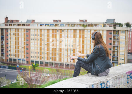 Young handsome eastern brunette girl listening music sitting on a small wall in the city suburbs, view from back - Stock Photo