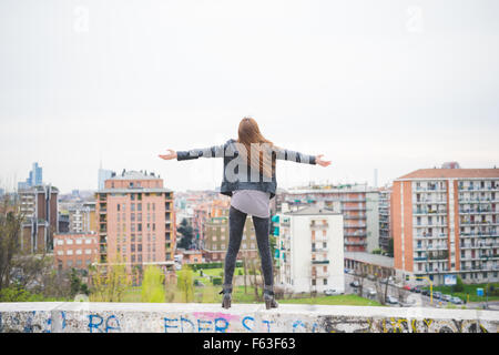 Young beautiful caucasian blonde girl with arms wide open feeling free in the suburbs standing on a small wall  - Stock Photo