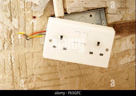 Electric plug sockets with exposed wiring in a rented social housing property house that needs attending to - Stock Photo