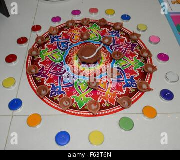 rangoli in a colorful and rainbow design with earthen diyas and multicolor candle - Stock Photo