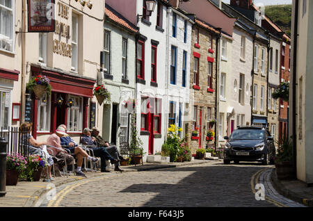 Car rounds the corner as people sit in the sun, relaxing outside pub - narrow cobbled High Street, quaint village of Staithes, North Yorkshire, UK.