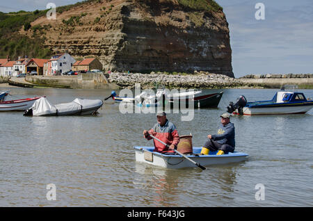 Sunny summer day, 2 fishermen are rowing to the shore in a small boat with their fishing catch  - sea harbour, Staithes' - Stock Photo