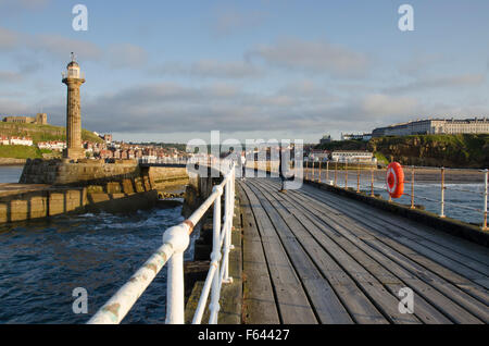 Sunny summer evening view of people relaxing on the West  Pier, Whitby, North Yorkshire, GB - scenic town, lighthouse - Stock Photo