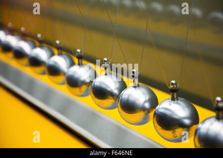Newton's cradle balancing large group of balls - Stock Photo