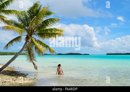 Female tourist bathing in the shallow water of the sea under a palm tree on a beach on a desert island in the lagoon - Stock Photo