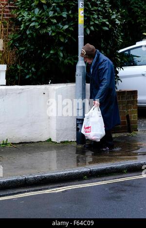 elderly man struggles to walk through a puddle uk - Stock Photo