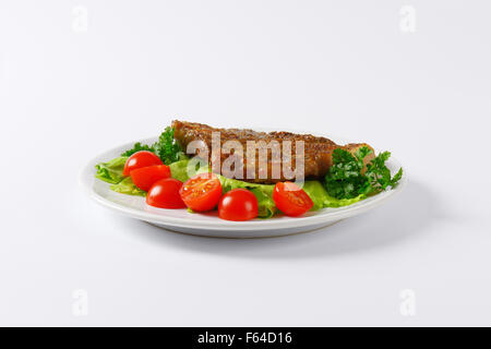 slice of roasted pork meat with vegetable garnish on white plate - Stock Photo