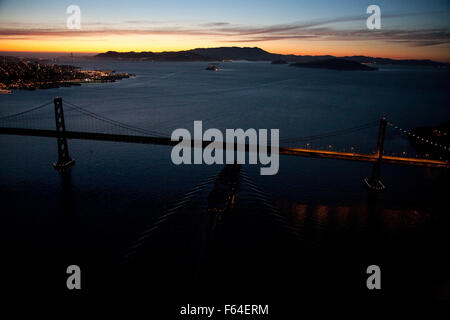 ship sailing on San Francisco Bay aerial view at night under Bay Bridge - Stock Photo