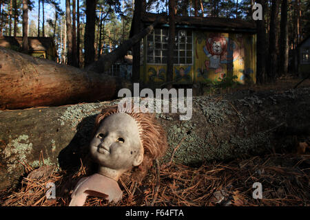 An orphaned doll in the abandoned holiday camp Izumrodnoe, located near the cooling pond of the Chernobyl nuclear - Stock Photo