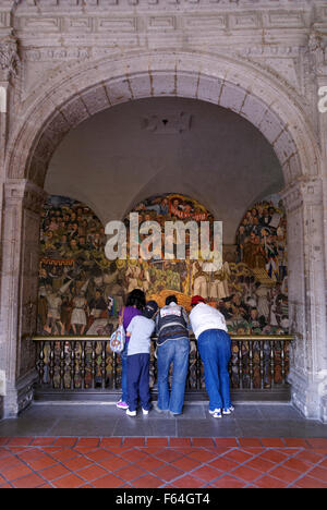 Mexican family looking at the Diego Rivera murals in the National Palace or Palacio Nacional, Mexico City - Stock Photo