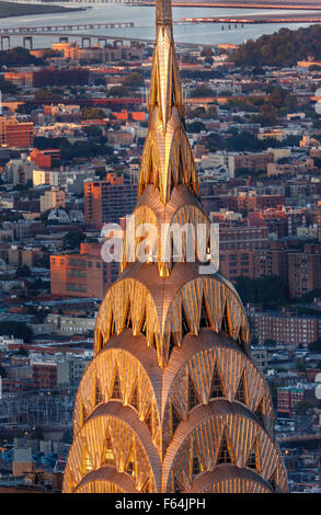 Detail of the Art Deco crown and spire of Chrysler Building in Midtown Manhattan at sunset. New York City aerial - Stock Photo