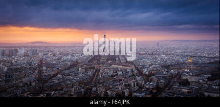 Panoramic aerial sunset view of Paris with the Eiffel Tower, La Defense and Invalides and storm clouds. France - Stock Photo