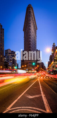 Flatiron Building with a clear blue sky and car light trails on 5th Avenue at dusk in Midtown Manhattan, New York - Stock Photo