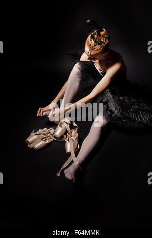 Slim ballerina in a black corset and black tutu tying pointe shoes. Classical Ballet. - Stock Photo