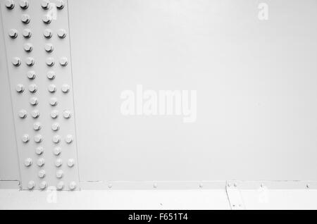 White steel wall with bolts in a row, metal parts connection, automotive bridge fragment - Stock Photo