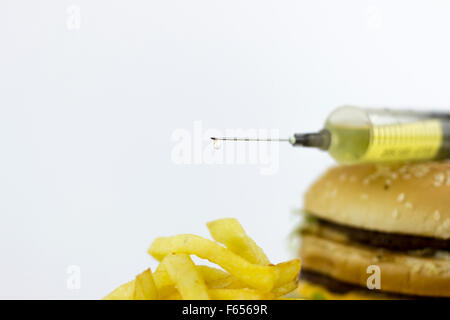 Syringe leaking yellow liquid on french fries - Stock Photo