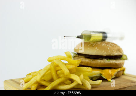 Syringe placed on a hamburger, leaking yellow liquid on french fries - Stock Photo