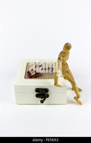 Wooden puppet sitting on a jewelry box on a white background - Stock Photo