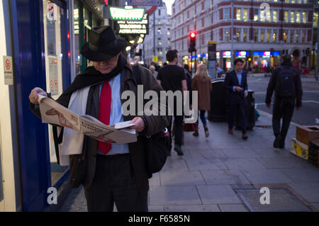 A city gent engrossed in the Evening Standard newspaper on a London street early evening - Stock Photo