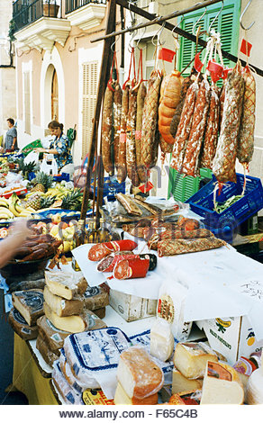 Cheeses and sausages displayed on market stall - Stock Photo