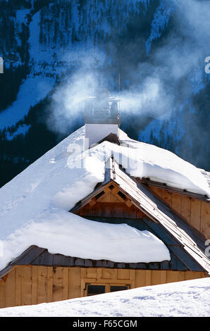 Chimney and snow covered roof of wooden hut - Stock Photo