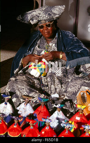 Herero woman wearing traditional dress sitting with hand made dolls, Namibia - Stock Photo