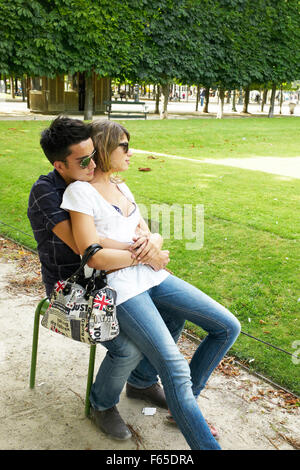Romantic couple sitting on chair in park, Paris - Stock Photo