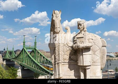 A statue of St Stephen in front of the Cave Church with a view of the Chain Bridge, Budapest, Hungary - Stock Photo