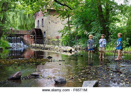 Three boys playing at the Knollmeyer Mühle, a water mill in Nettetal, Wallenhorst - Stock Photo