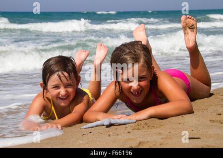 Happy girls on the beach with starfish - Stock Photo