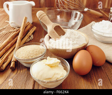 Ingredients to make a cake or a dessert on an aged wooden table - Stock Photo
