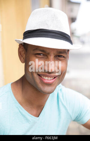 Head shot of any ethnic man smiling wearing a light blue green t-shirt and black and white fedora - Stock Photo