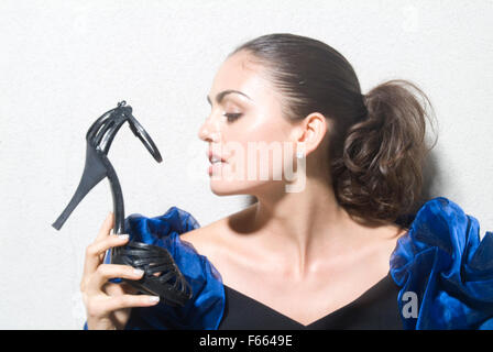 Girl in a luxury dress holding a shoe against a white while.  She is looking away from the camera. - Stock Photo