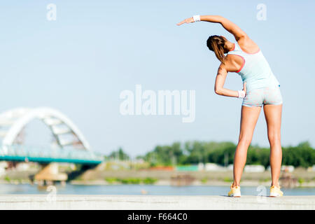 Young woman stretching and relaxing in the city before exercise - Stock Photo